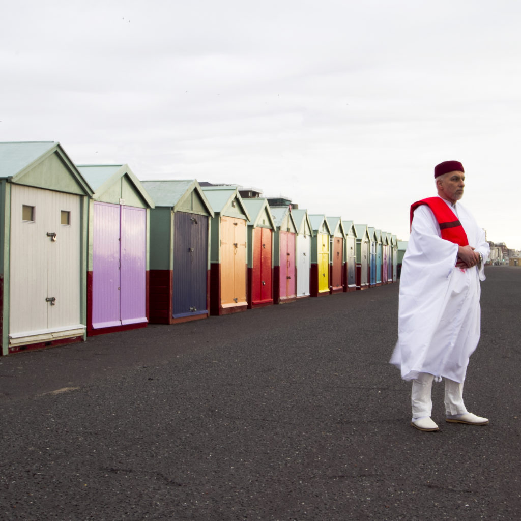 A man wearing a long Islamic style white robe over white trousers, with a red scarf and red cap, stands in front of brightly coloured beach huts on Hove seafront