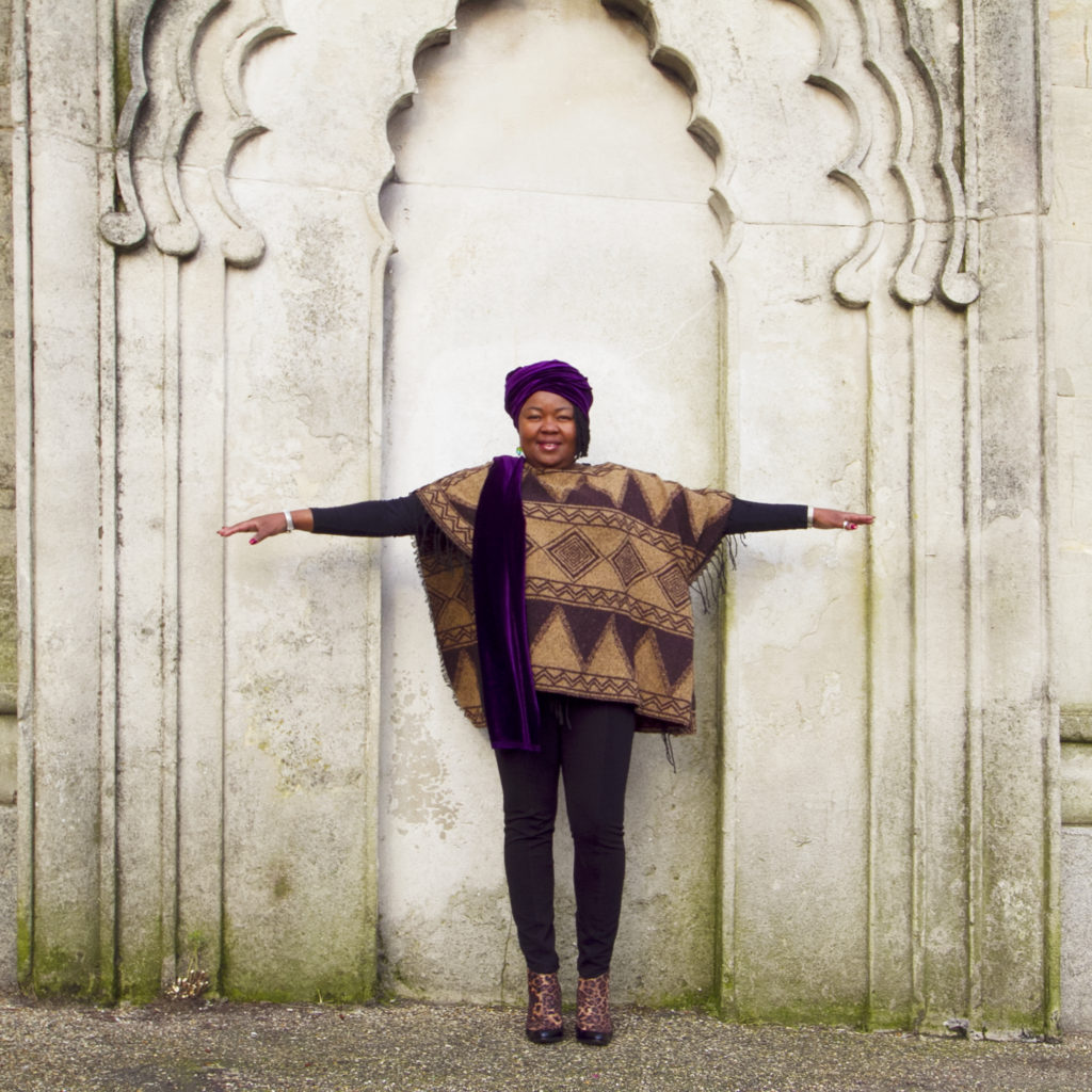 A woman stands with her arms outstretched in front of an Indian style arch on the Royal Pavilion estate, wearing a geometric print brown and black poncho over a black top and leggings, and a purple headwrap.