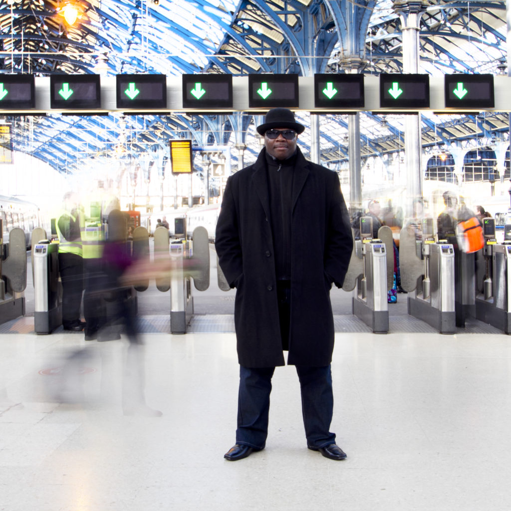 A man in a black bowler hat, sunglasses and a long black overcoat over a black suits stands in Brighton station