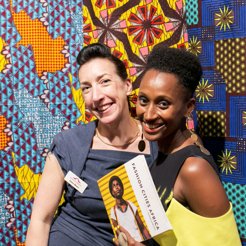Curator Helen Mears and writer Hannah Azieb Pool pose with the Fashion Cities Africa book in front of brightly coloured Dutch wax print fabrics