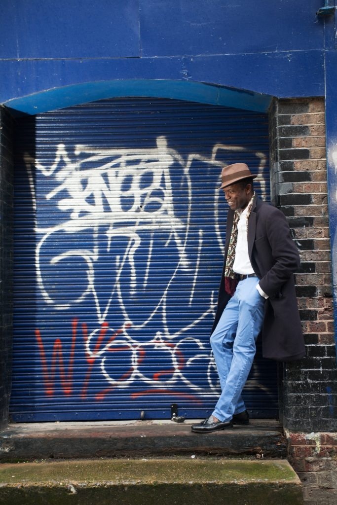 A man wearing a brown trilby, long black trench coat, white shirt and blue jeans stands in a blue doorway next to a shuttered shopfront