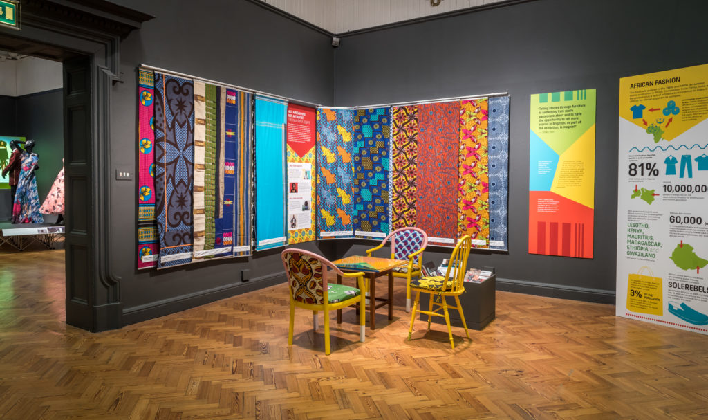 A museum gallery with dutch wax print panels on the walls, and colourful chairs upholstered in wax print