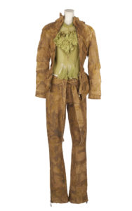 A mannequin wearing a brown leather camouflage print bomber jacket and matching trousers, with a pale green frilly blouse