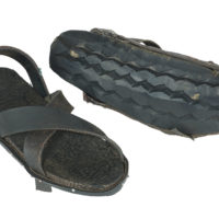 Two black rubber sandals, one turned to show that the sole is made from a car tyre