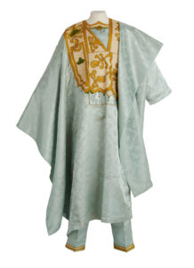 a mannequin wearing a long pale blue satin robe and matching trousers. The robe has islamic inspired golden embroidery at the chest and on the hem of the trousers.