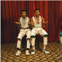 Colour photograph of two men seated in portrait studio, wearing white vest tops and white trousers, holding beadwork.