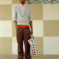 Colour photograph of a young man wearing brown trousers, a red striped shirt and grey jumper, accessorised with a grey hat, red sunglasses and belt, and a checked shopping bag