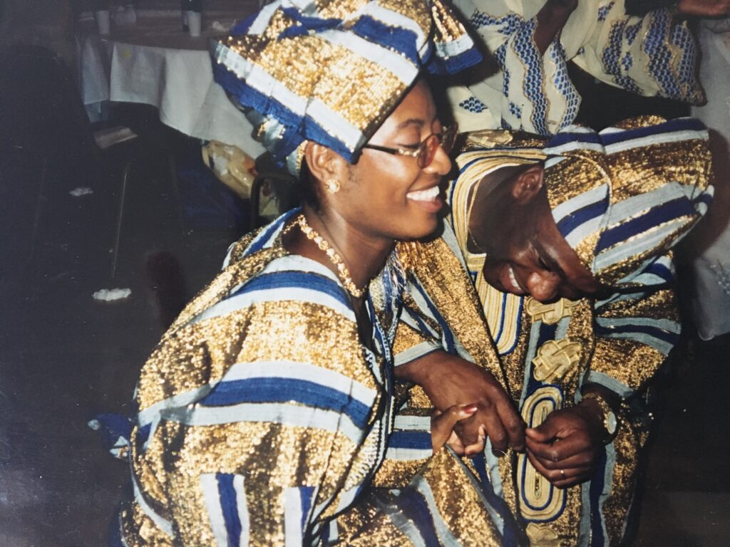 a young Black couple wearing aso-oke dance at their wedding