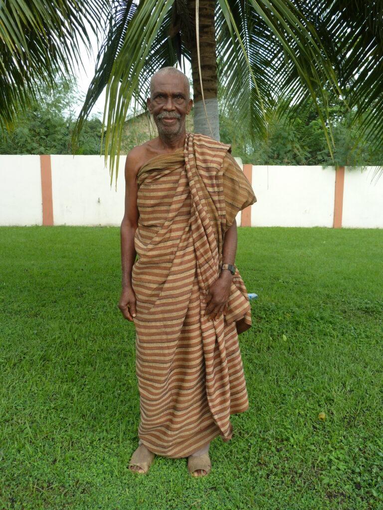 an older man wearing a kente standing in a garden