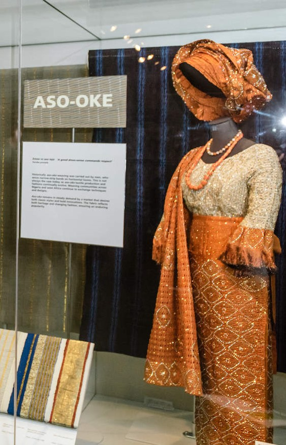 Museum display of orange and gold aso-oke outfit