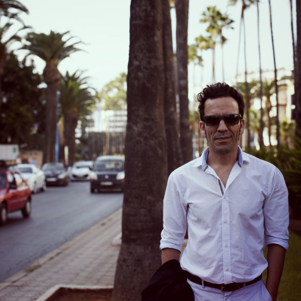 Said Mahrouf standing in a morroccan street with palm trees, wearing a white shirt and sunglasses