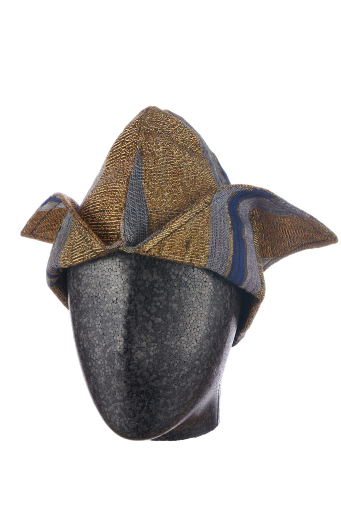 a man's blue and gold aso-oke cap with two triangular flaps on a mannequin head
