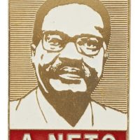 Rectangular shaped metal badge featuring a portrait of Agostinho Neto in white enamel.