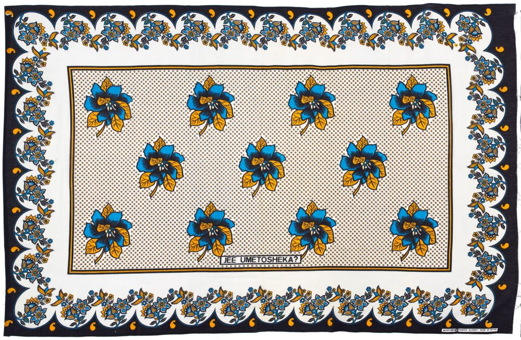 Kanga with a black border, white background, blue and yellow flower designs and yellow spots.