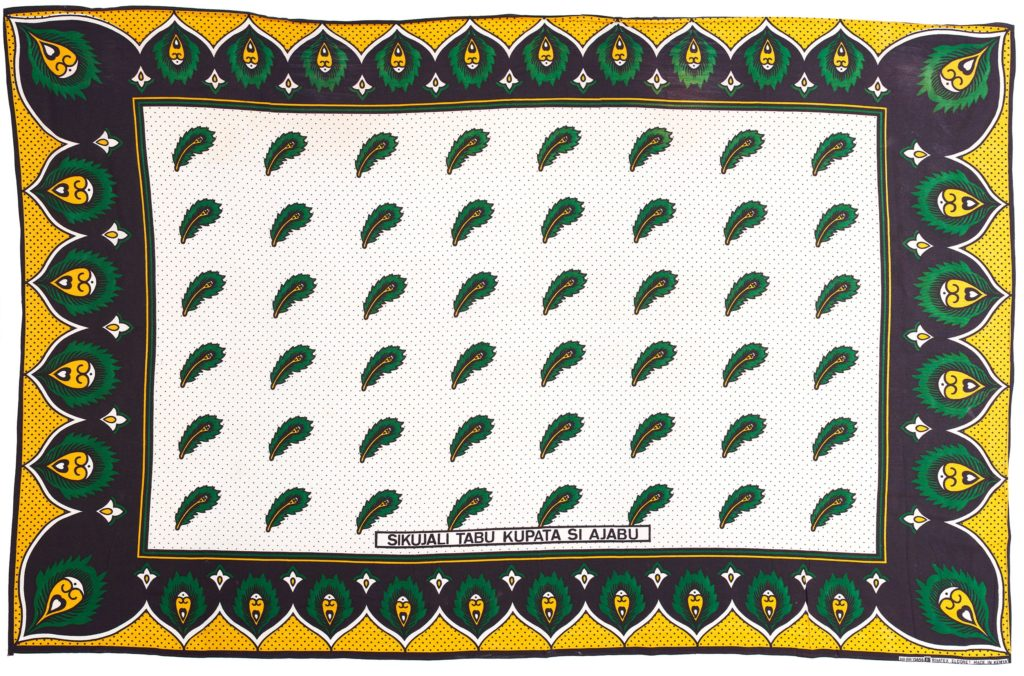 Kanga with indigo border with green and yellow feather motif and yellow scallops with indigo spots, white central panel with indigo spots and green and yellow feather motifs.