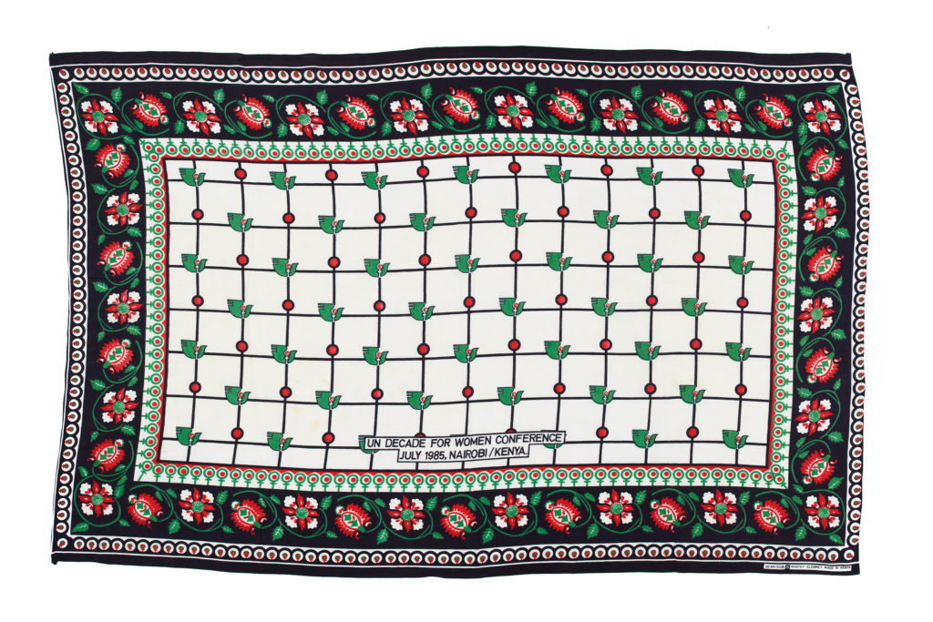 white kanga with black and red floral border, with a central repeat pattern of doves and female symbols