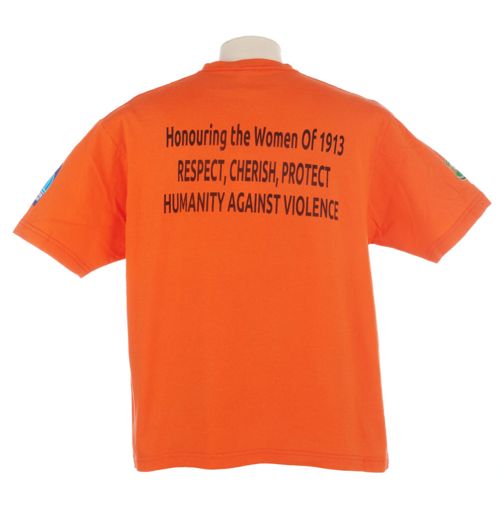 Back view of orange T shirt with the slogan 'Honouring the Women of 1913'