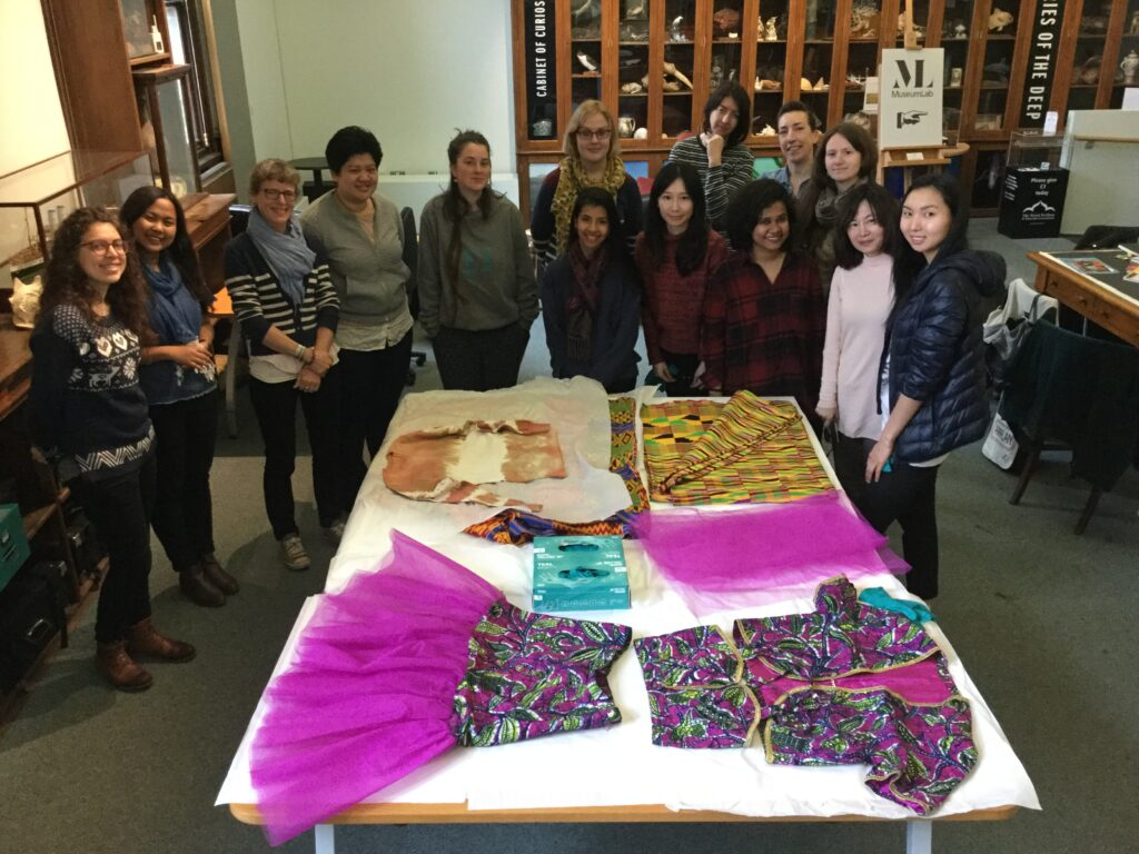 A group of students looking at textiles and garments laid out on a table.