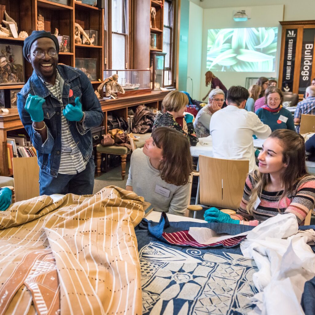 visitors look at textiles laid out on table