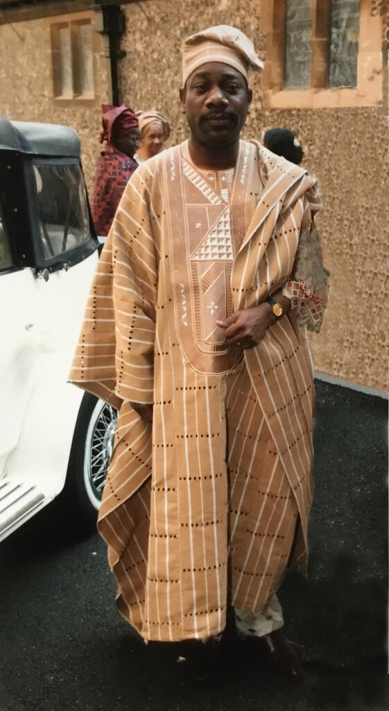 A Nigerian man wearing a beige aso-oke outfit at a wedding