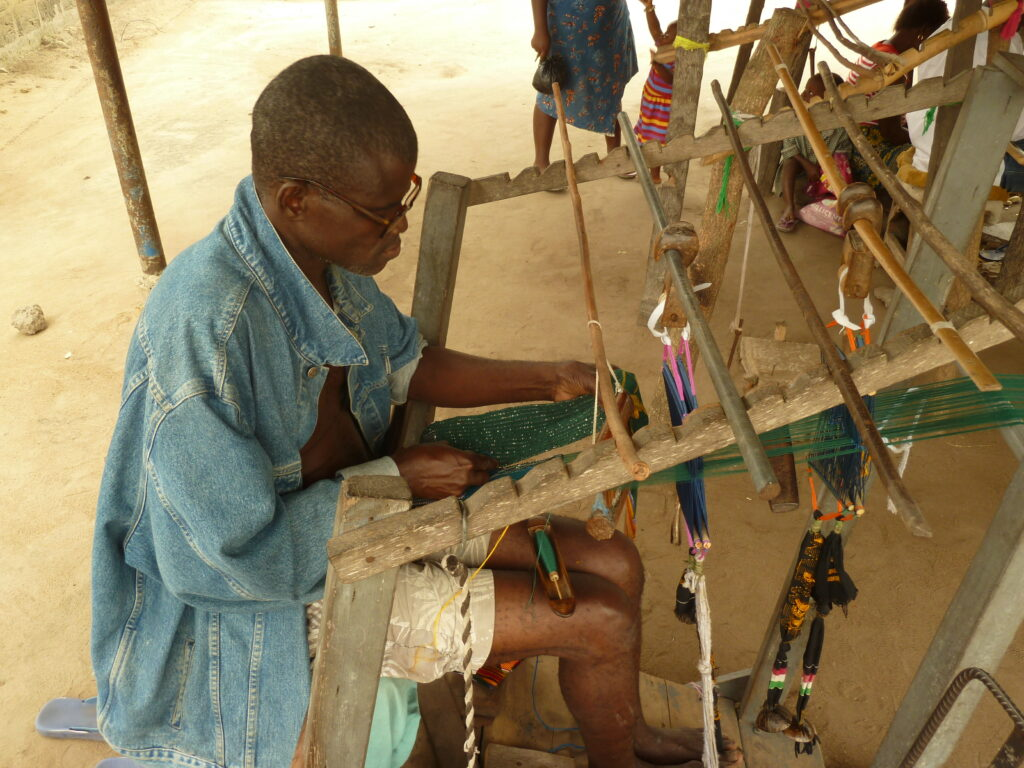 a man weaving a kente cloth at a large wooden loom