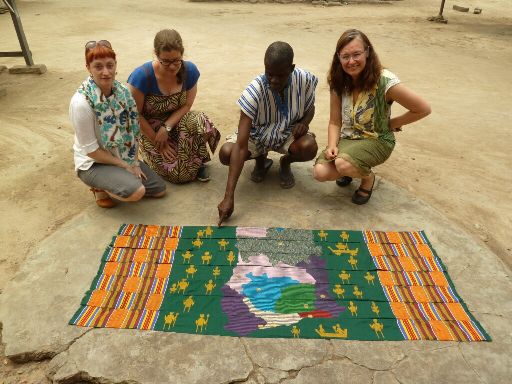 three women and a man crouch on the ground next to a kente cloth