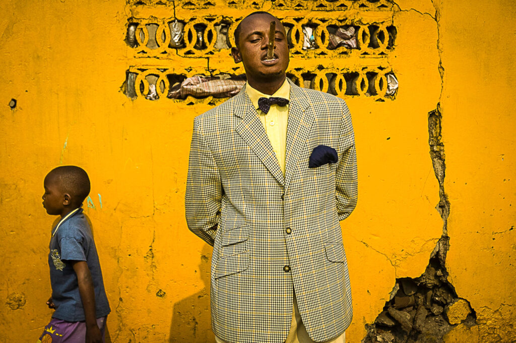 Colour photograph of a young man in a checked single breasted suit jacket with his hands behind his back, standing in front ot a yellow wall. A young boy in a blue T shirt is walking past on the left of the frame.