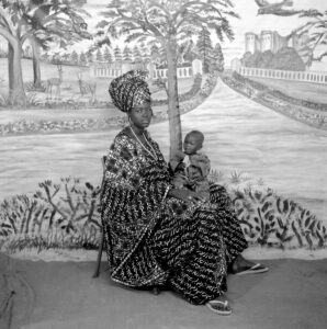 Studio portrait of a woman wearing voluminous robes, headwrap and flipflops, with a small child in her lap.