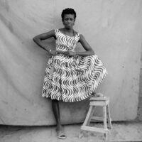 Portrait of a woman in a sleeveless, knee-length print dress with a full skirt, posing with her hands at her waist and one leg on a stool, in front of a cloth backdrop.