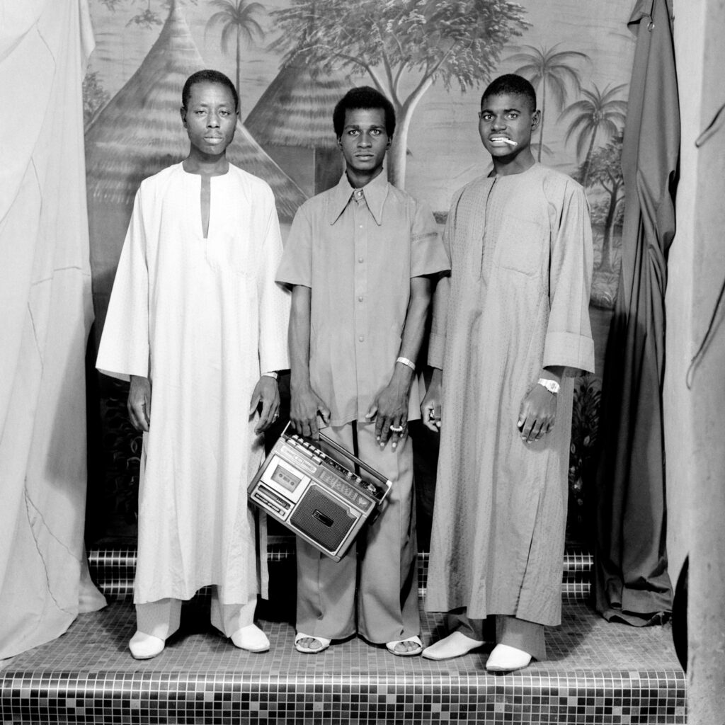 Studio portrait of three men standing in front of a painted cloth backdrop, one holding a portable stereo.