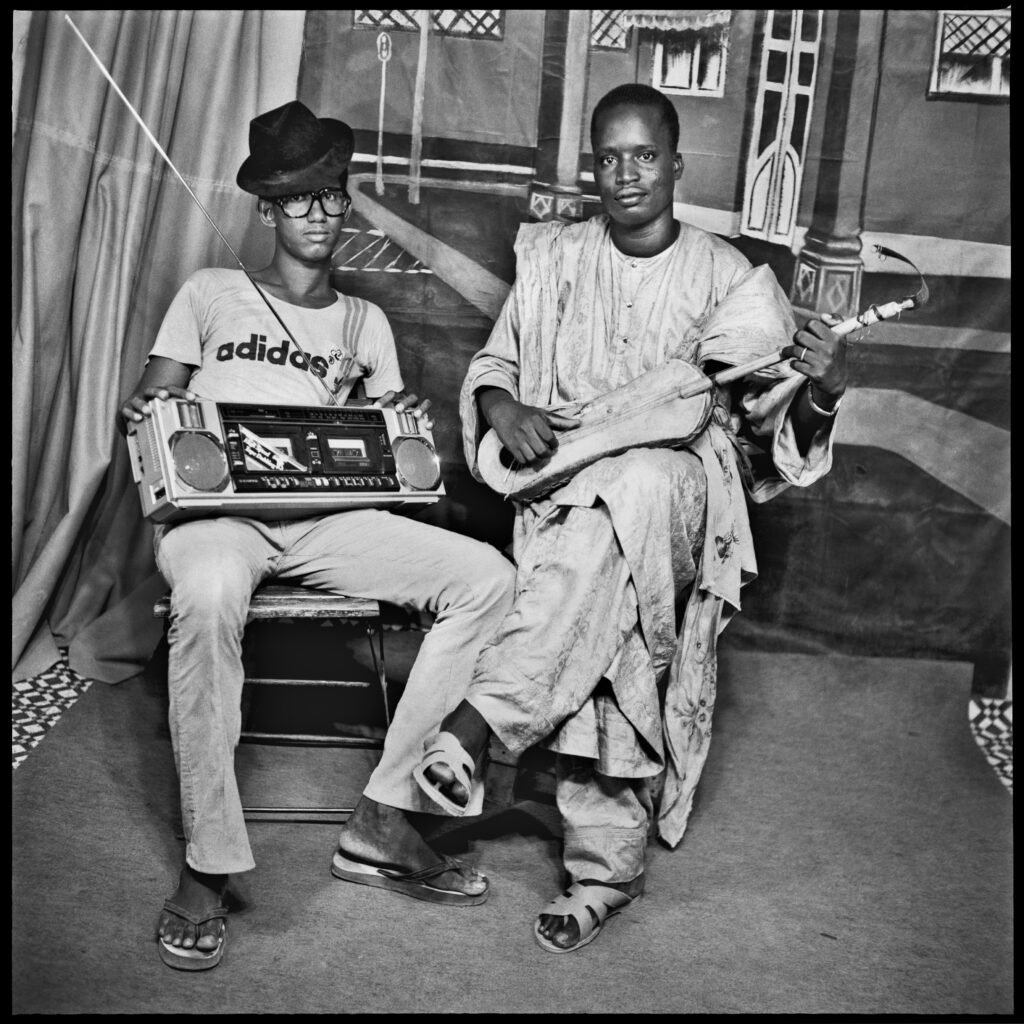 Studio portrait of two young men, one wearing an Adidas T shirt and black hat, holding a portable stereo on his lap. The other man is wearing a long robe and has a stringed musical instrument.