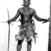 Black and white photograph of man in vest and shorts with hunting gear and bow and arrow