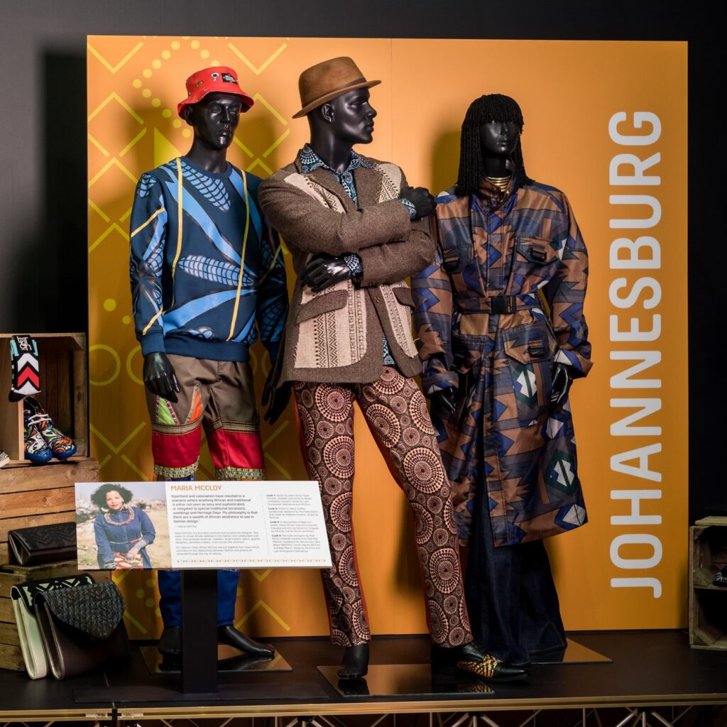 Museum display of three mannequins dressed in contemporary outfits from South Africa
