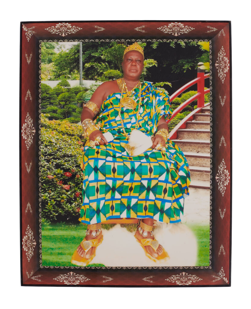 a formal portrait of a war chief wearing a green and blur kente