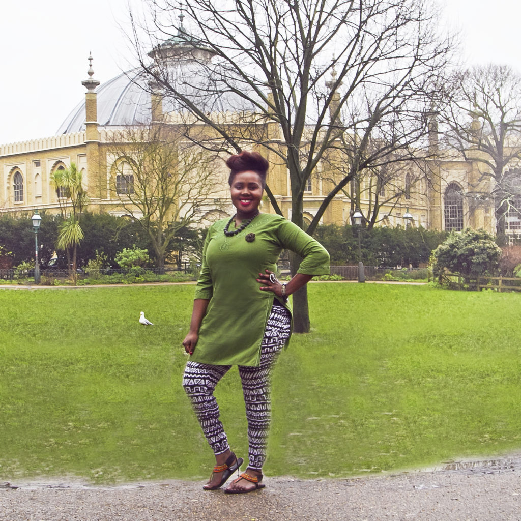 A woman stands in the Pavilion Gardens in Brighton wearing a long green tunic top over black and white print leggings