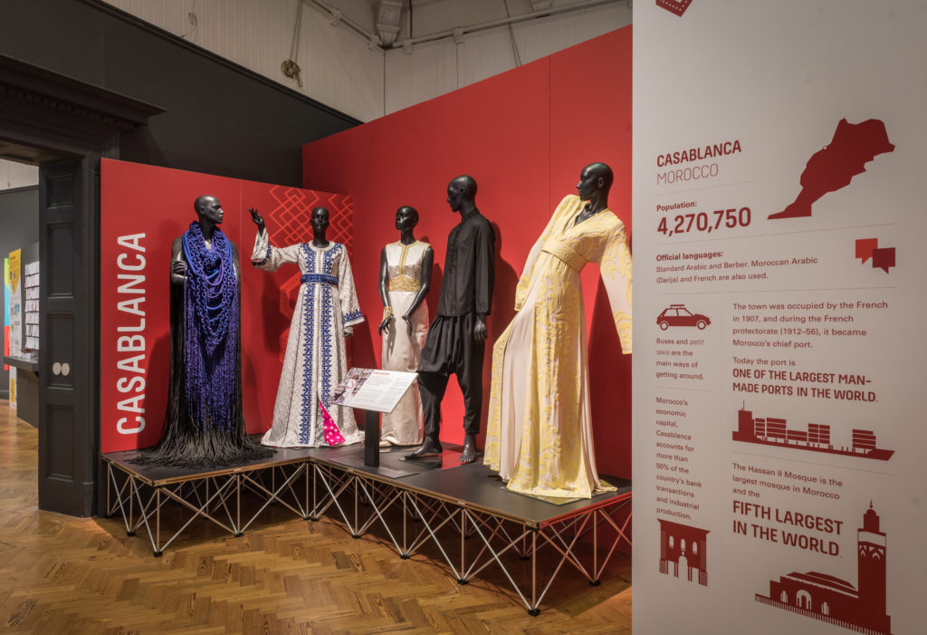 A museum display with five mannequins wearing outfits from Moroccan designers