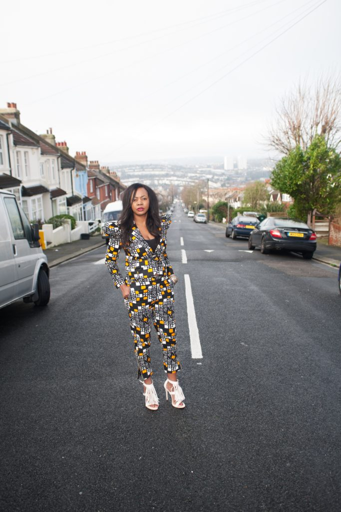 A woman wearing a dutch wax print trouser suit and white fringed sandals stands on a Brighton street