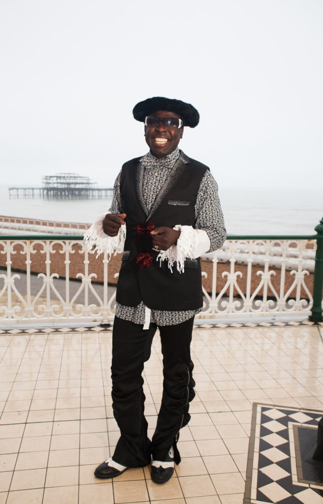 A man stands on Brighton bandstand wearing a black hat, grey shirt with white feather cuffs, black waistcoat and black trousers with black and white brogues