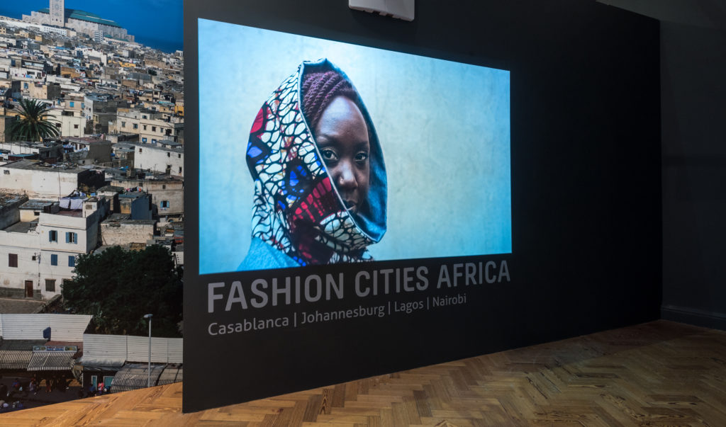 An exhibition panel from Fashion Cities Africa, featuring a woman wearing a brightly coloured dutch wax print hood.