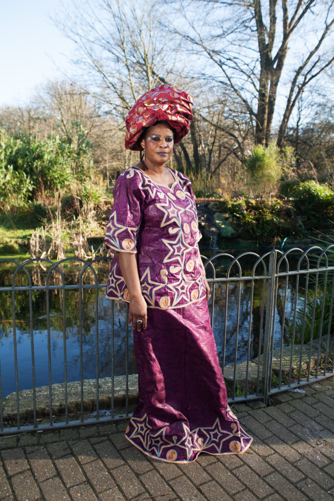 A woman wearing a purple blouse and matching skirt, with a red headwrap