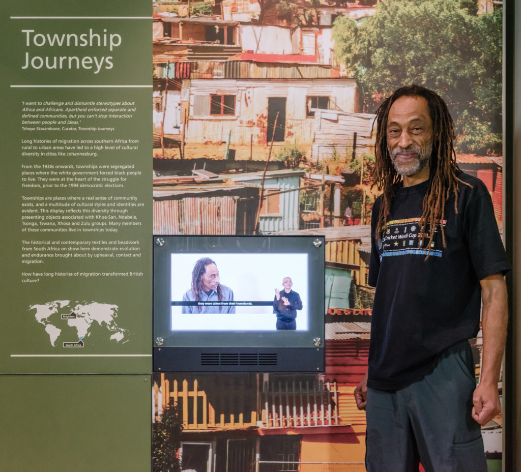 Curator Tshepo Skwambane stands next to the Township Journeys museum display