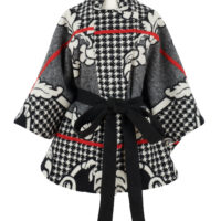 A woman's cape coat made from a black, white and red woollen basotho blanket.