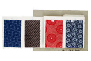 Four swatches of shweshwe fabric in a sample book