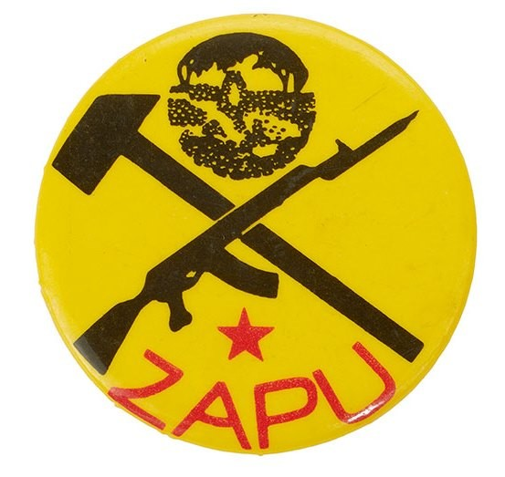 Round yellow pin badge reading 'ZAPU' in red letters, underneath a gun crossed with a hammer.