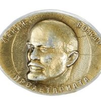 Oval shaped metal pin badge featuring a portrait of Lenin with Russian text.