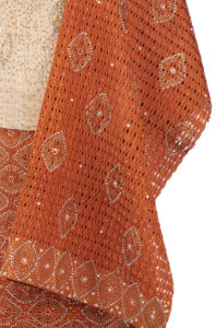 detail of orange and gold aso-oke fabric embellished with sequins and gems