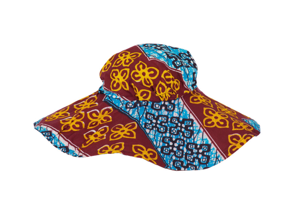 Woman's hat with a wide brim made of wax print fabric, blue and maroon with yellow flower motif.