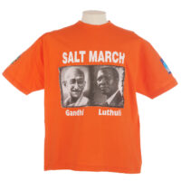 Orange Salt March T shirt with black and white portraits of Gandhi and Luthuli on the front