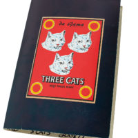 cardboard sample book with three white cat faces on a red background with a black border