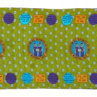 green printed cloth with repeat illustrated pattern of two black women reading from a book